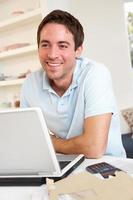junger Mann, der mit Laptop arbeitet foto