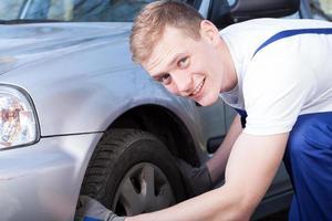 Automechaniker überprüft einen Autoreifen foto