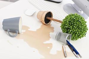 umgestürzte Pflanze und verschütteter Kaffee auf dem Schreibtisch