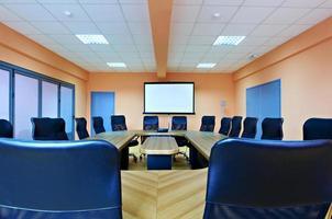 Konferenzraum mit leeren Stühlen und einer Projektionswand foto