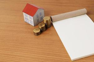 Papierhaus, Münzenstapel, Notizblock für Hypothekendarlehenskonzept foto