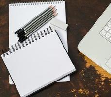zwei Skizzenblöcke, Bleistifte, Radiergummi und Laptop foto