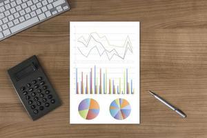 Diagramm auf dem Desktop mit Tastatur und Taschenrechner foto