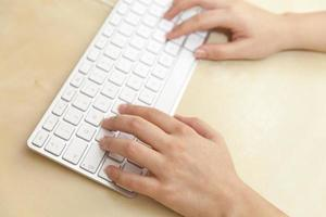 weibliche Hände, die auf Tastatur auf hölzernem Schreibtisch tippen foto