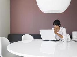 nachdenklicher Geschäftsmann mit Laptop am Schreibtisch foto