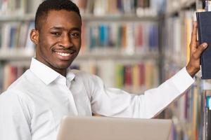 glücklicher männlicher Student, der mit Laptop in Bibliothek arbeitet