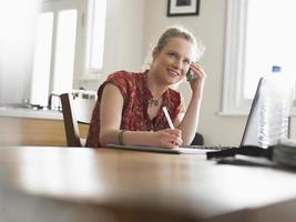 Frau auf Abruf schreibt Notizen am Esstisch foto
