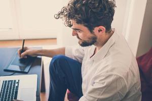 schöner Hipster moderner Mann, der nach Hause mit Laptop arbeitet foto