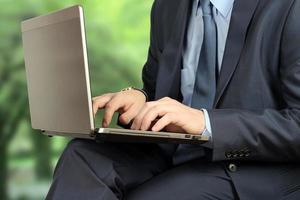 junger Geschäftsmann, der mit einem Laptop arbeitet, draußen sitzt, Bäume dahinter foto
