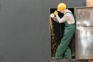 Arbeiter im orangefarbenen Helm mit Winkelschleifer foto