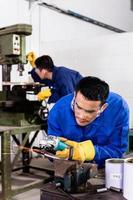 Metallarbeiter im industriellen Werkstattschleifen foto