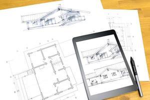 Arbeitsplatz mit digitalem Tablet und Plänen foto