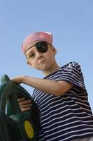 Junge hält ein Lenkrad als Pirat verkleidet foto