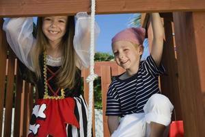 glückliches Mädchen als Pirat verkleidet, der mit Freund spielt