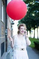 lockiges blondes Mädchen mit großem roten Ballon am Telefon foto