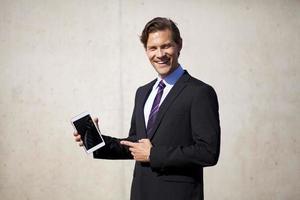 Geschäftsmann zeigt auf Tablette foto