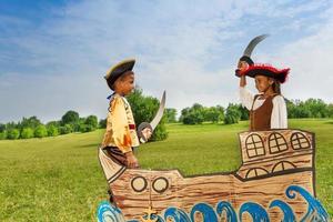 zwei afrikanische Kinder als Piraten, die sich mit Schwertern duellieren foto