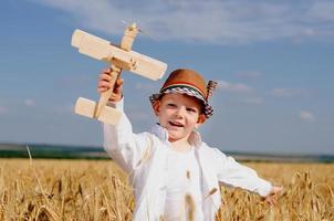 trendiger Junge, der in einem Feld mit einem Flugzeug spielt