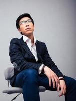 nachdenklicher junger Geschäftsmann, der auf dem Stuhl sitzt foto