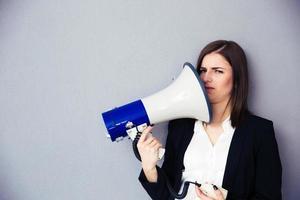 junge Geschäftsfrau zeigt Megaphon auf sich
