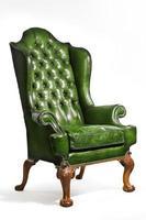 antiker grüner Lederflügelstuhl geschnitzte Beine isoliert foto