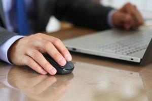 Hände des Geschäftsmannes im Anzug, der die drahtlose Computermaus hält foto