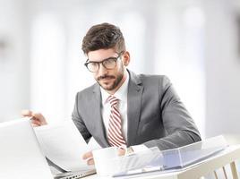 Geschäftsmann am Schreibtisch, der Papierarbeit tut