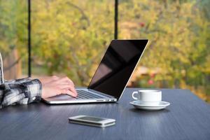 Person, die am hölzernen Schreibtisch am Computer-Kaffeetelefon arbeitet foto