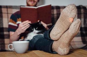 junger Mann, der Buch mit Katze in löchrigen Socken liest foto