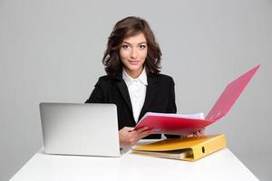ziemlich selbstbewusste Sekretärin, die mit Computer und bunten Ordnern arbeitet foto
