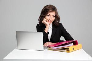 schöne lächelnde Geschäftsfrau mit Laptop und Bindemitteln foto