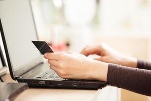 Nahaufnahme der Frau, die Kreditkarte hält und Laptop verwendet foto