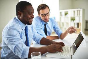 zwei Geschäftsleute, die sich auf einem Laptop beraten foto