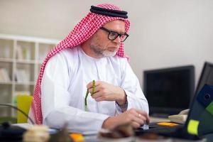 Porträt eines intelligenten arabischen Geschäftsmannes unter Verwendung des Laptops foto