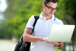 Student liest ein Thema auf seinem Laptop foto