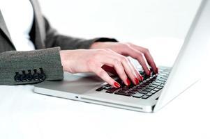 Nahansicht der Frauenhände unter Verwendung des Laptops foto