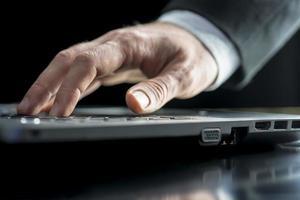 Geschäftsmann, der auf einem Laptop-Computer tippt foto