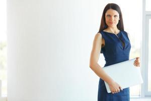 Geschäftsfrau mit Laptop-Computer, der im Büro steht. foto