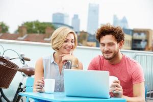 junges Paar, das auf Dachterrasse mit Laptop sitzt