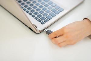 Nahaufnahme auf Geschäftsfrau, die USB-Blitz in Laptop setzt foto