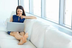 Porträt der lächelnden Geschäftsfrau unter Verwendung des Laptops im hellen Büro foto