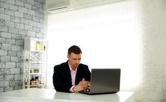 Geschäftsmann sitzt am Tisch mit Laptop foto
