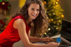 Porträt der glücklichen jungen Frau mit Kreditkarte unter Verwendung des Laptops foto