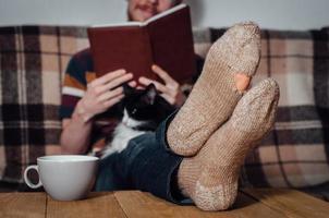 junger Mann, der Buch auf Kutsche mit Katze in Socken liest foto