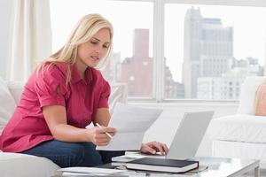 eine Frau, die einen Laptop benutzt und Papierkram liest