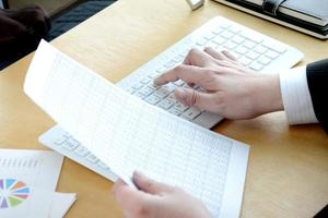 Hand des Geschäftsmannes mit Laptop