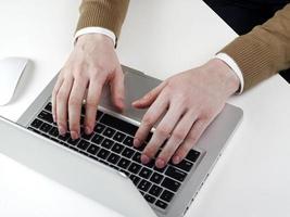 Mann, der auf Laptop schreibt foto