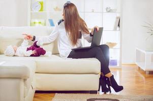 berufstätige Mutter, die von zu Hause aus arbeitet foto