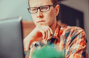 nachdenklicher Mann, der über dem Laptop arbeitet foto