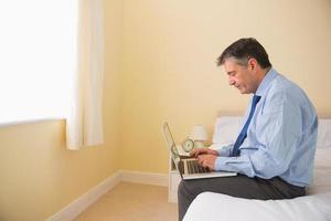 fokussierter Mann mit seinem Laptop auf einem Bett sitzend foto